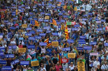 People hold placards and flag as they take part in a march of unity after last week attacks, in Barcelona, Spain, August 26, 2017. REUTERS/Albert Gea